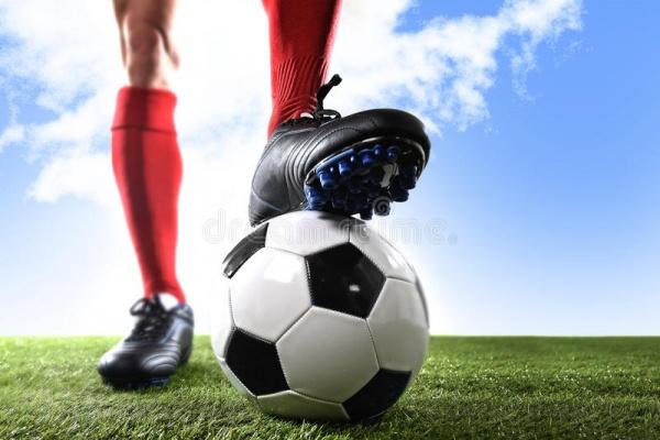 sluit-omhoog-de-voetbalster-van-benenvoeten-rode-schokken-en-zwarte-schoenen-die-met-bal-stellen-die